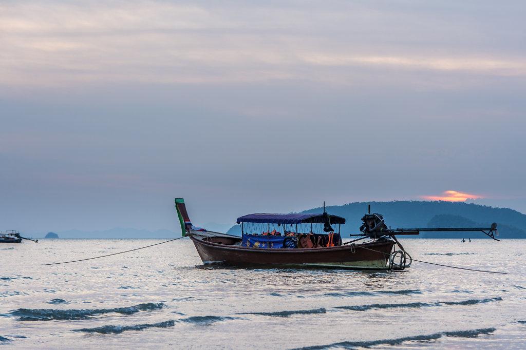 a traditional long boat at the beach of phuket, thailand